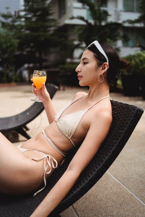 Seductora Joven étnica Tomando El Sol En La Tumbona Y Bebiendo Jugo