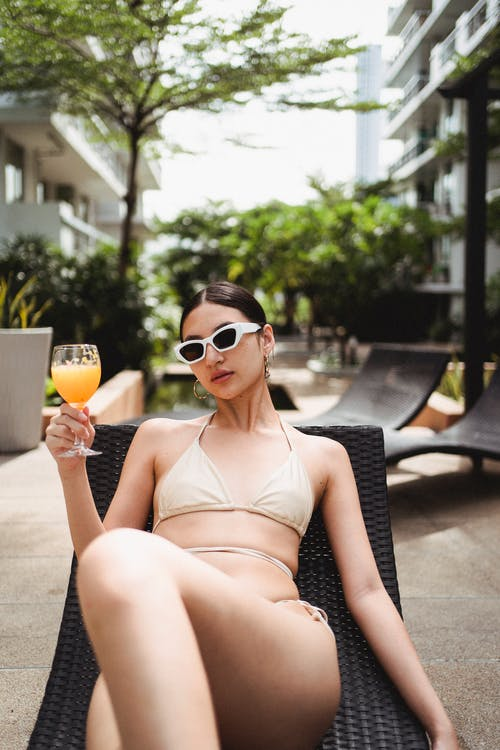 Alluring young slim ethnic woman in bikini and sunglasses chilling on sunbed at poolside of modern hotel and enjoying refreshing juice