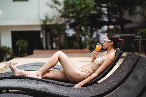 Side view of young ethnic barefooted lady in stylish swimwear and sunglasses drinking cold orange juice while sunbathing at poolside in modern hotel