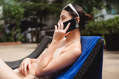 Young slim ethnic lady talking on mobile phone while sitting on sunbed in hotel yard