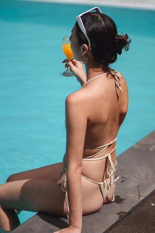 Side view of unrecognizable young sexy female traveler in bikini drinking orange juice while relaxing on edge of swimming pool on sunny day