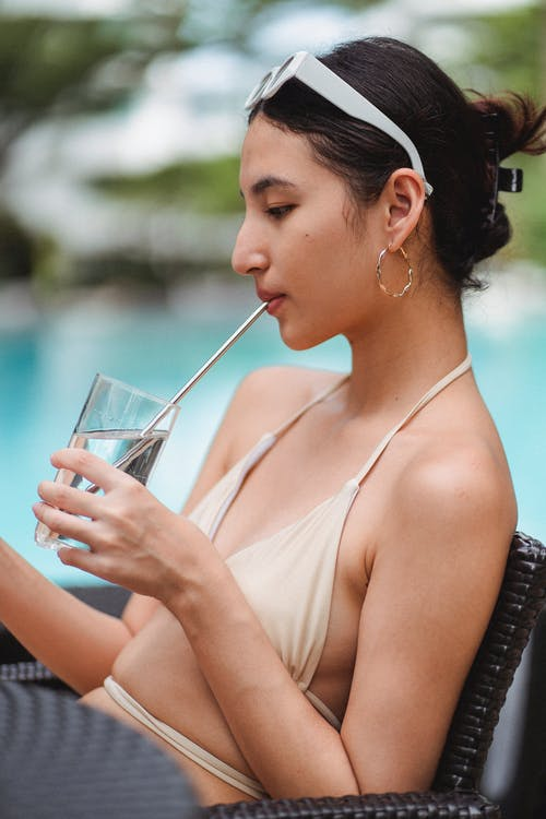 Stylish young ethnic brunette drinking glass of water in cafe at poolside