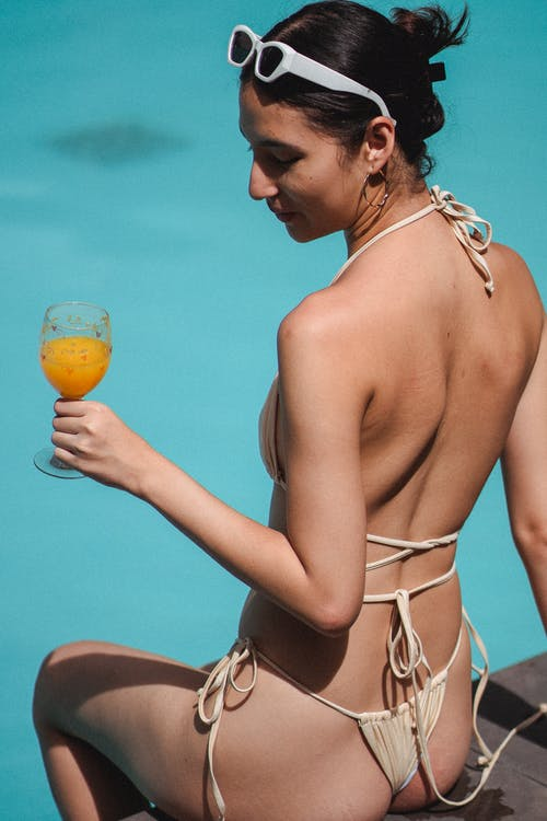 Back view of young sensual ethnic lady in sexy bikini drinking orange juice while chilling on swimming pool edge on sunny day
