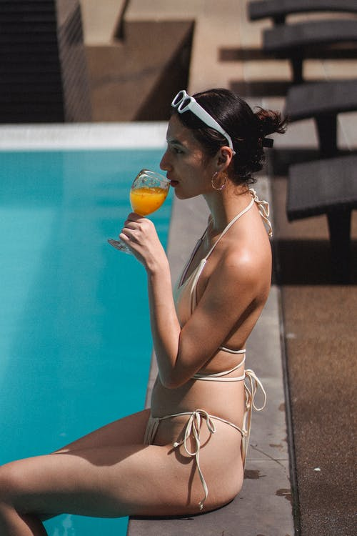 Side view of relaxed tanned young ethnic woman in bikini drinking fresh orange juice while sitting on pool border on sunny day