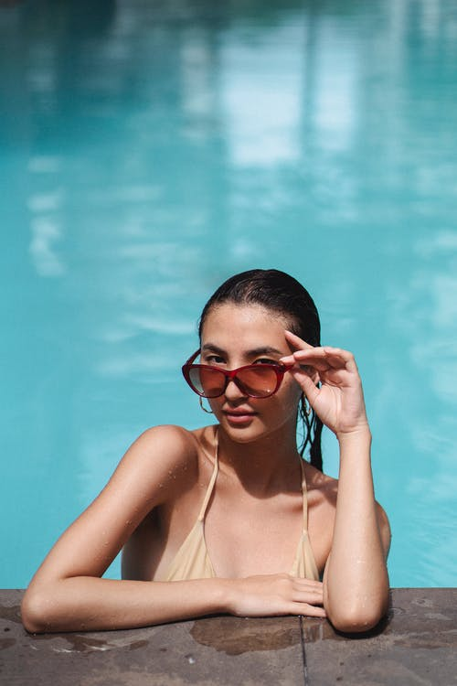 Pretty young female in beige swimwear chilling in swimming pool and leaning on poolside while lowering trendy sunglasses and looking at camera alluringly