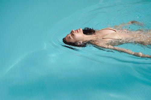 Content young female in beige bikini swimming with eyes closed in swimming pool and enjoying warm sun rays