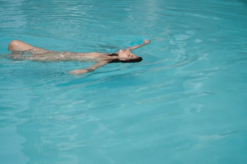 Serene young brunette with eyes closed swimming backstroke in pool water on clear day