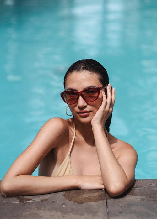 Gorgeous fit brunette in beige bikini and stylish sunglasses leaning on poolside and touching face gently while looking at camera seductively