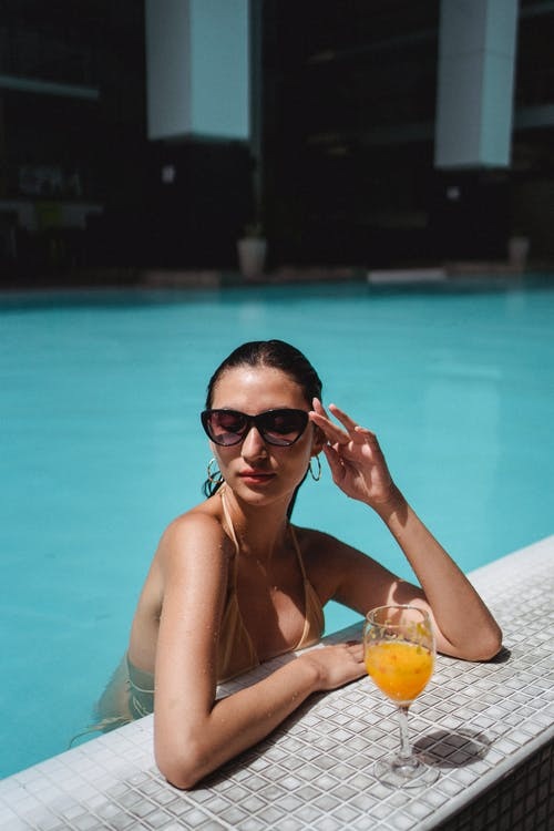 Beautiful tanned female wearing bikini and trendy sunglasses relaxing in outdoor pool with glass of refreshing orange juice while touching face gently