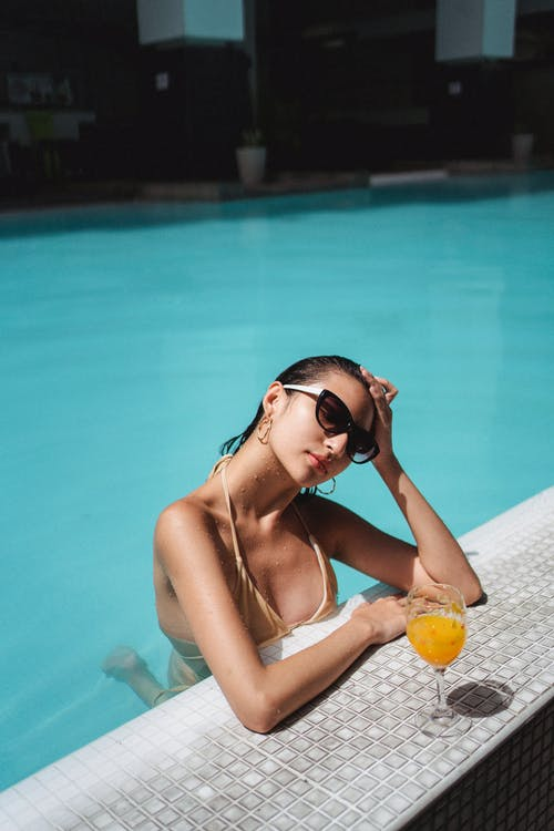 Beautiful tanned woman chilling in swimming pool with orange juice
