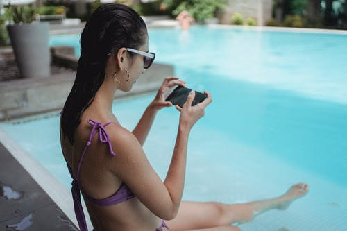 Fit woman chilling on poolside and taking picture of legs