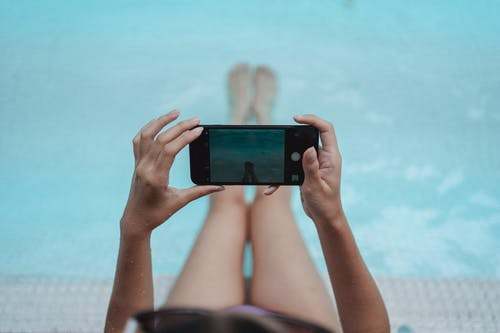 High angle crop anonymous female with fit body relaxing on poolside and taking picture of legs