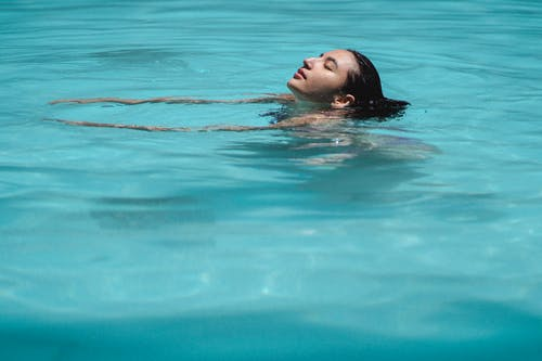 Relaxed ethnic woman swimming in pool with closed eyes