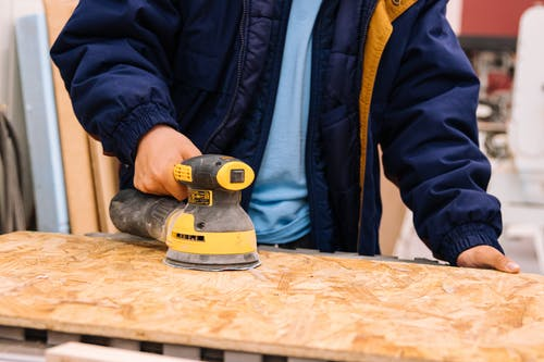 Person in Blue Jacket Holding Black and Yellow Cordless Hand Drill