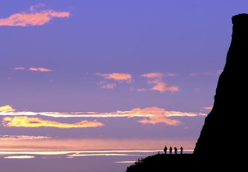 Silhouette of People Standing on Rock Formation during Sunset
