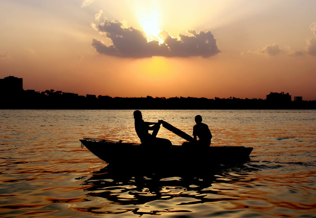 Silhouette of 2 Person Riding on Boat during Sunset