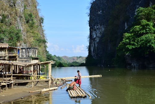 Side view of anonymous men constructing bamboo boat on seashore amidst rocky cliffs in Ha Long Bay on sunny day