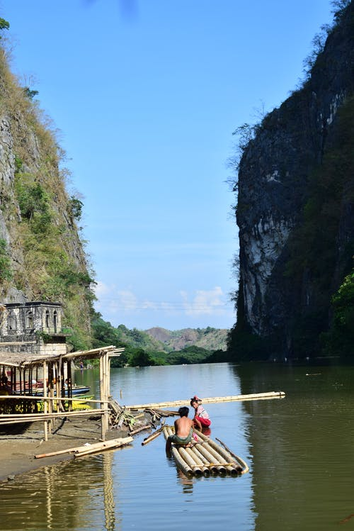 Unrecognizable indigenous people building traditional bamboo boat in sea surrounded by rocky mountains against blue sky in Ha Long Bay