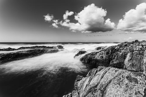 Clouds in sky over rocky shore of stormy sea