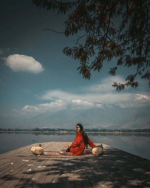 Woman in Red Dress Sitting on Brown Wooden Dock