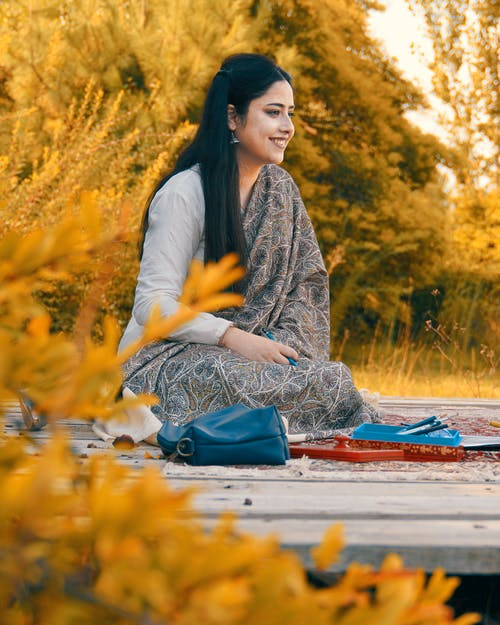 Woman in White Long Sleeve Shirt Sitting on Red and Blue Textile on Ground