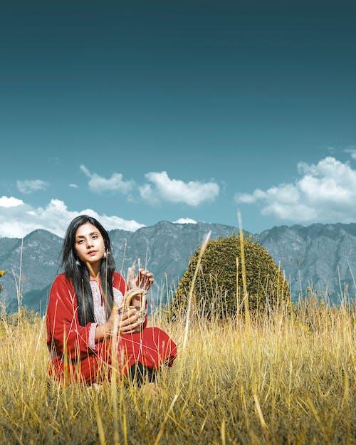 Woman in Orange Long Sleeve Dress Sitting on Green Grass Field