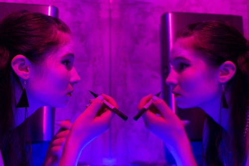 Side view of female with dark hair looking at reflection in mirror while applying makeup in room with neon light