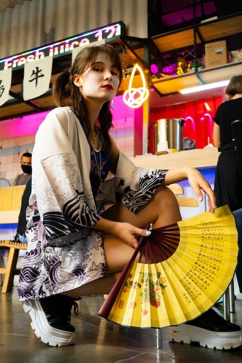 Stylish woman squatting with fan