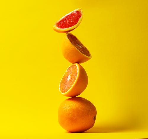 Orange Fruit on Yellow Surface