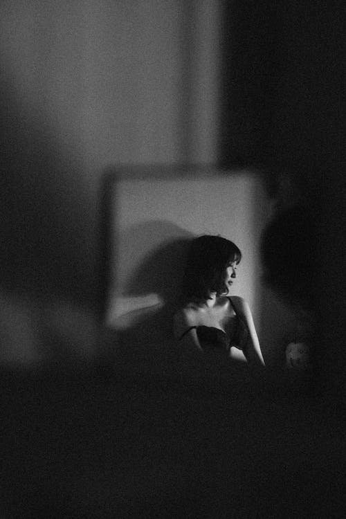 Through window frame black and white of unrecognizable distant female in bra leaning and casting shadow on wall in dark room while looking away