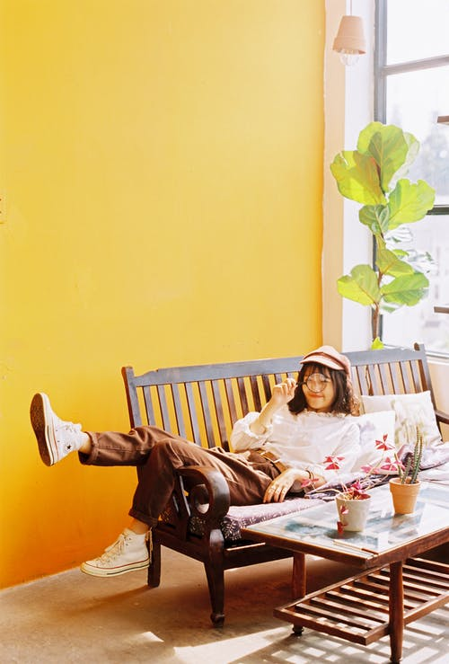 Full body of young Asian female in cap lying on wooden bench with magnifier in hand near table with potted plants in room with yellow wall