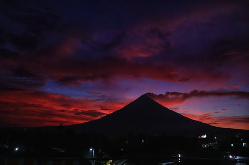 Colorful sunset above volcano near settlement at twilight