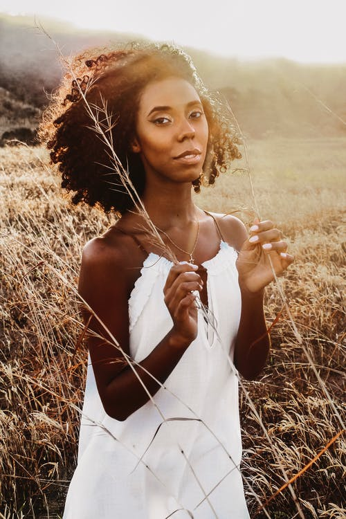 African American female in white dress standing in grassy field in summer evening time under sunlight and looking at camera