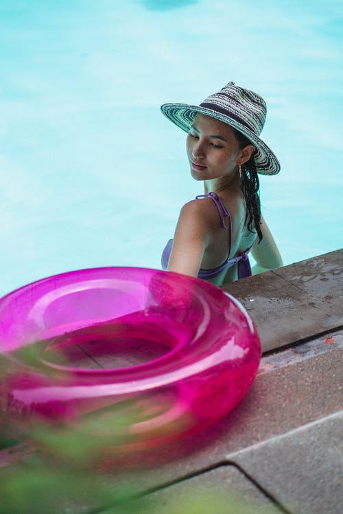 High angle back view of young female wearing swimsuit and hat enjoying vacation in blue swimming pool