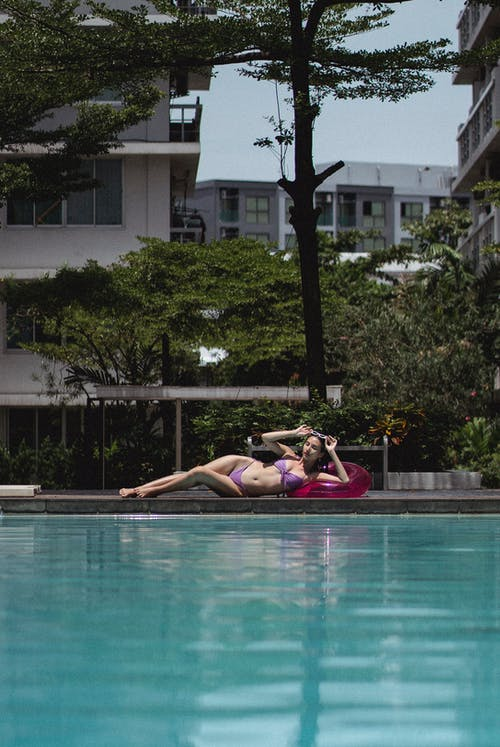Graceful woman lying on poolside in sunny poolside