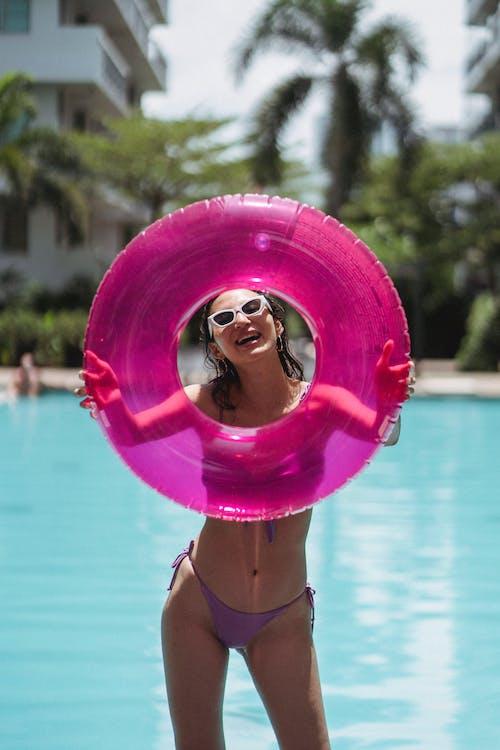 Cheerful woman in bikini holding swimming ring in front