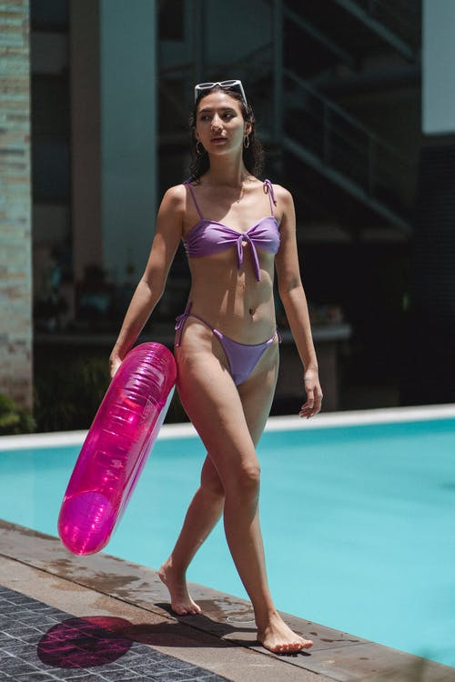 Attractive woman walking on poolside with swimming ring