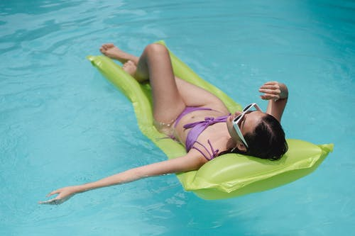 Full body fit young female in swimwear and trendy sunglasses lying on inflatable pool bed and sunbathing