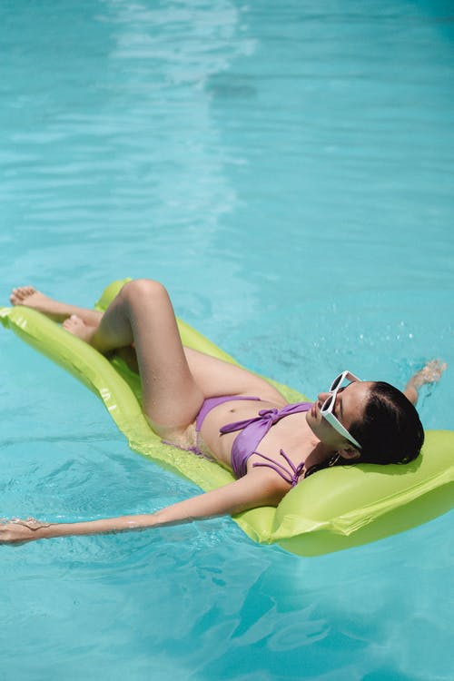 Woman lying on inflatable mattress on pool water