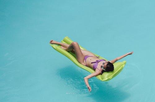 Female in swimwear sunbathing on inflatable mattress in pool