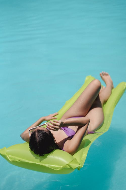 Slim female resting on inflatable mattress in swimming pool