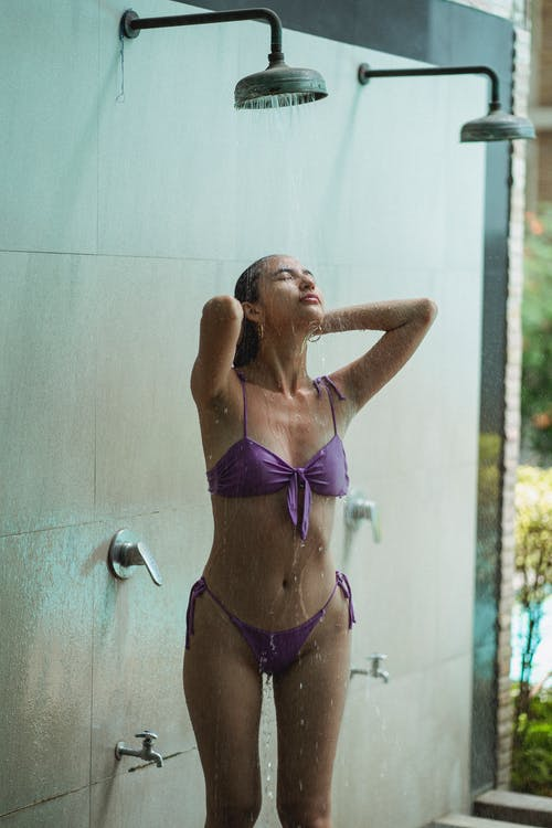 Slim young lady in swimsuit taking spacious shower next to swimming pool in resort