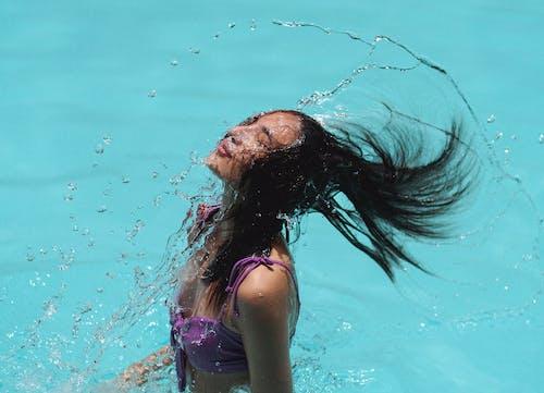 在度假村游泳池的蓝色水中纤细的波浪状头发