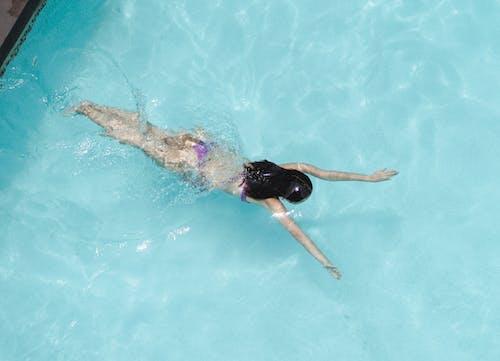 Anonymous woman in bikini swimming in clear pool