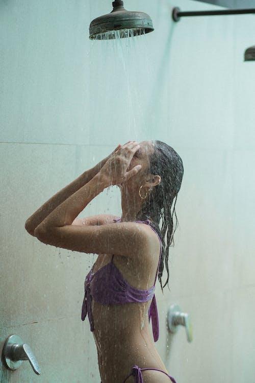 Sensual woman in bikini under stream in shower