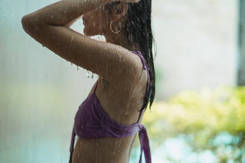 Side view of crop sensual slim female wearing lilac swimsuit standing in shower and raising hands to rinse off hair on blurred background
