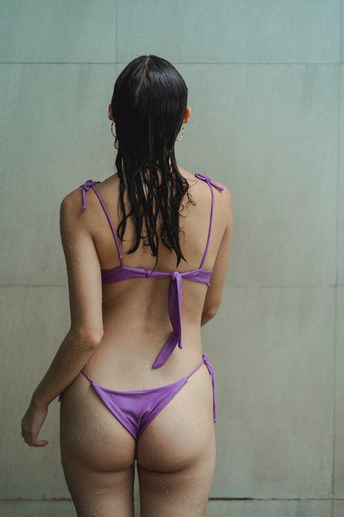 Back view of anonymous sensual woman wearing violet bikini standing in bathroom with wet skin and hair