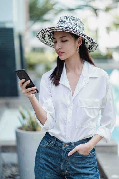 Young attractive Asian woman wearing trendy clothes and straw colorful hat standing on terrace and browsing cellphone on summer day