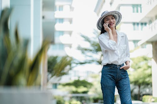 Positive stylish young female talking on cellphone on city street