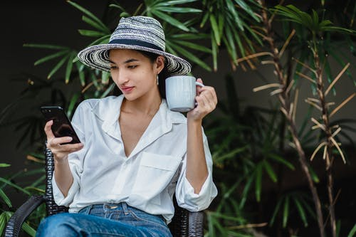 Young Asian lady wearing stylish outfit sitting in wicker armchair in greenery and browsing smartphone while drinking hot beverage